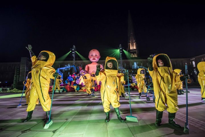 Three people in yellow hazmat suits hold brooms, gazing outward. It is night time and they are standing on a square somewhere. Behind them is a big white inflatable baby, more people in yellow hazmat suits, and a circus playground. Two tall pillars beam out green light onto the scene.