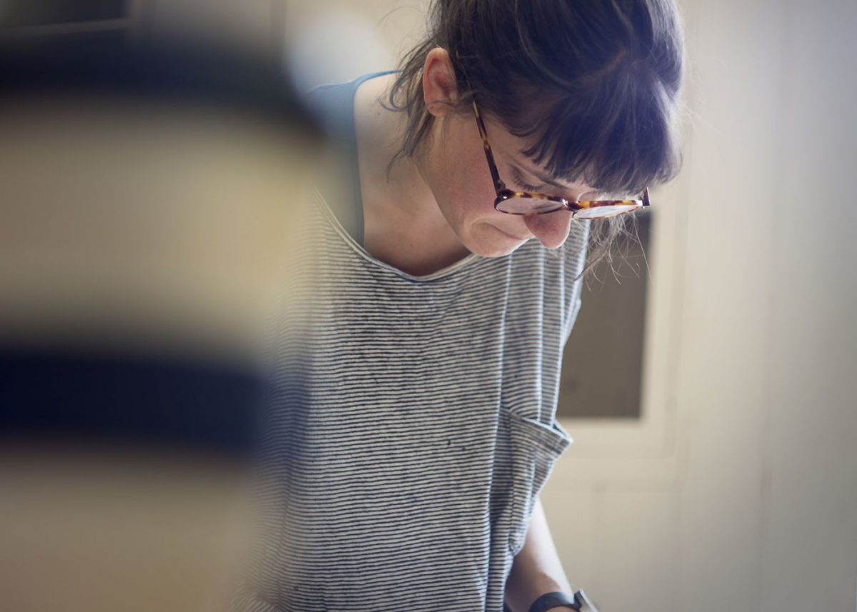 Person wearing glasses standing and leaning over, looking at something beneath them