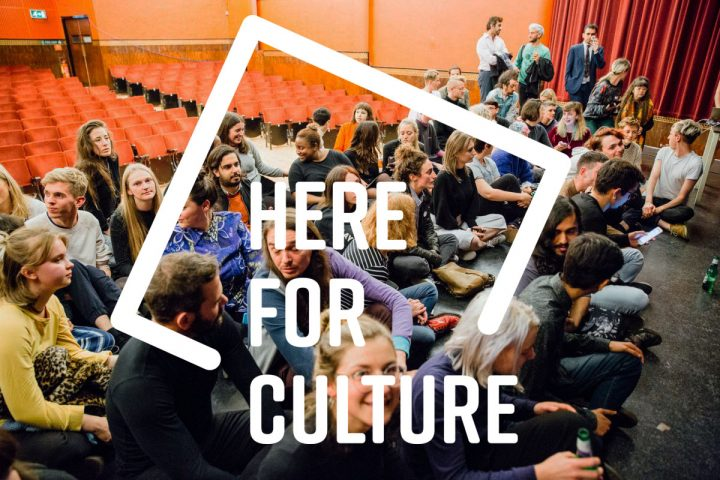 A graphic of Here for Culture overlaid on a photograph of audiences sitting on a stage in a theatre