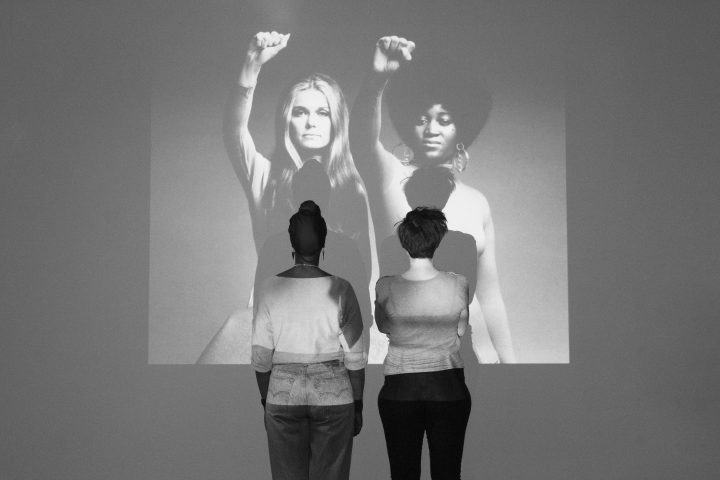Anna-Maria Nabirye and Annie Saunders stand in front of a projection of a portrait of Dorothy Pitman-Hughes and Gloria Steinem