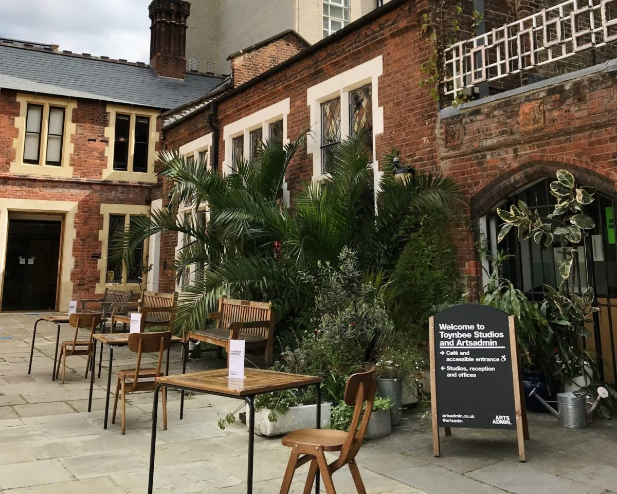Outside of a red brick building with palm trees, tables and chairs on a courtyard