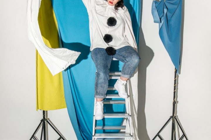 Person sits at the top of a ladder wearing a top with very long sleeves