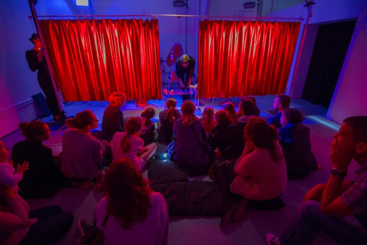 Seated audience of around 20 people watching a performer on stage arranging objects on a table. There are red curtains in the background on railings