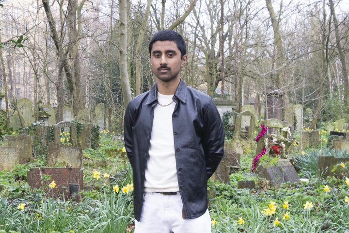 person standing in cemetery wearing black leather jacket, white jumper and white jeans