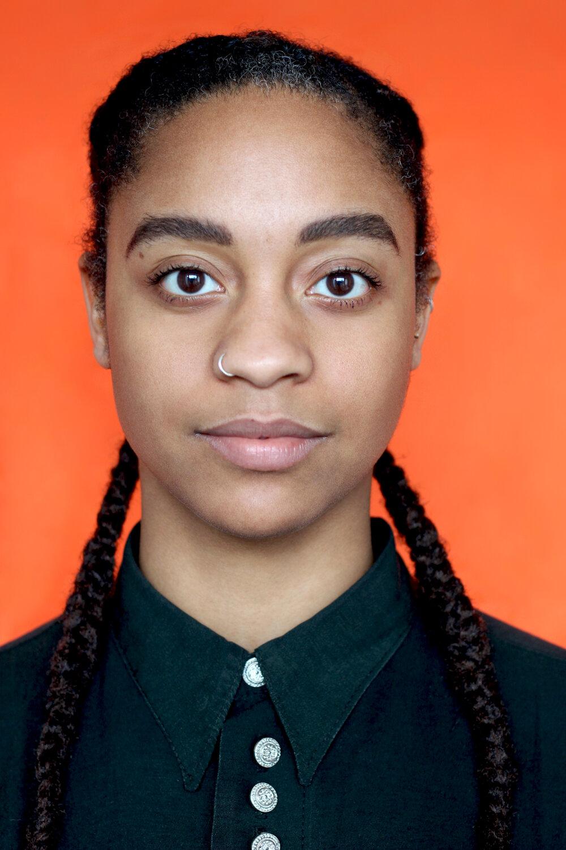 Portrait of Lateisha wearing a black shirt against an orange background