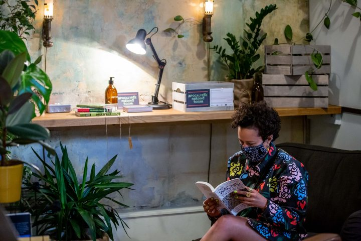 person sitting on an armchair reading a book, wearing a mask. They are surrounded by plants, books and lamps