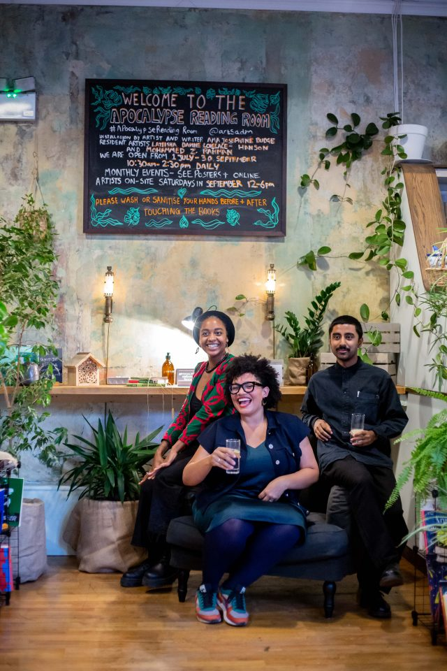 3 people on an armchair surrounded by books and plants in the corner of a cafe