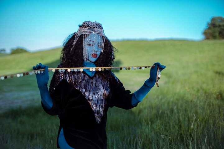 person painted blue with head jewellery holding a chain, standing in a field
