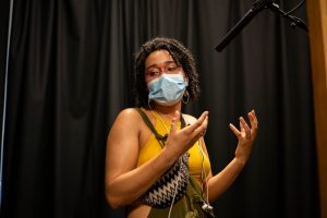 womxn wearing mask speaking with hand gestures. A mic is overhead.