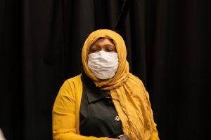 womxn wearing mask sitting