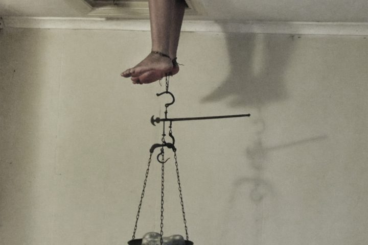persons legs hanging through attic access with a weight dish hanging from the persons ankles