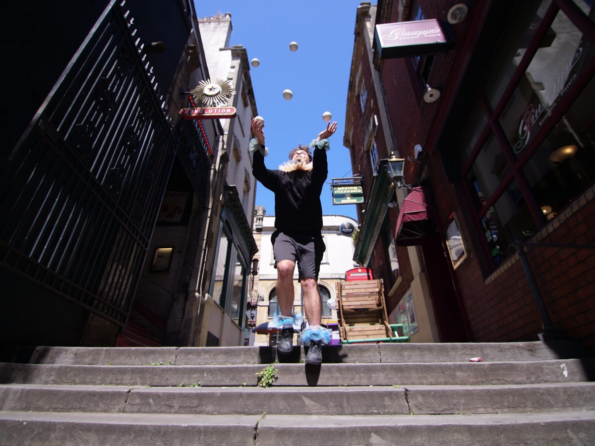 Circus performer at the top of stone steps, standing and juggling