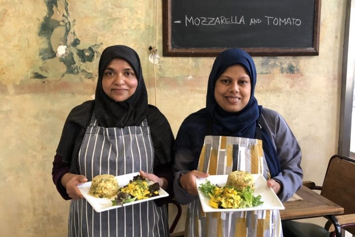 Two people in a cafe wearing aprons and holding plates of salads and quinoa