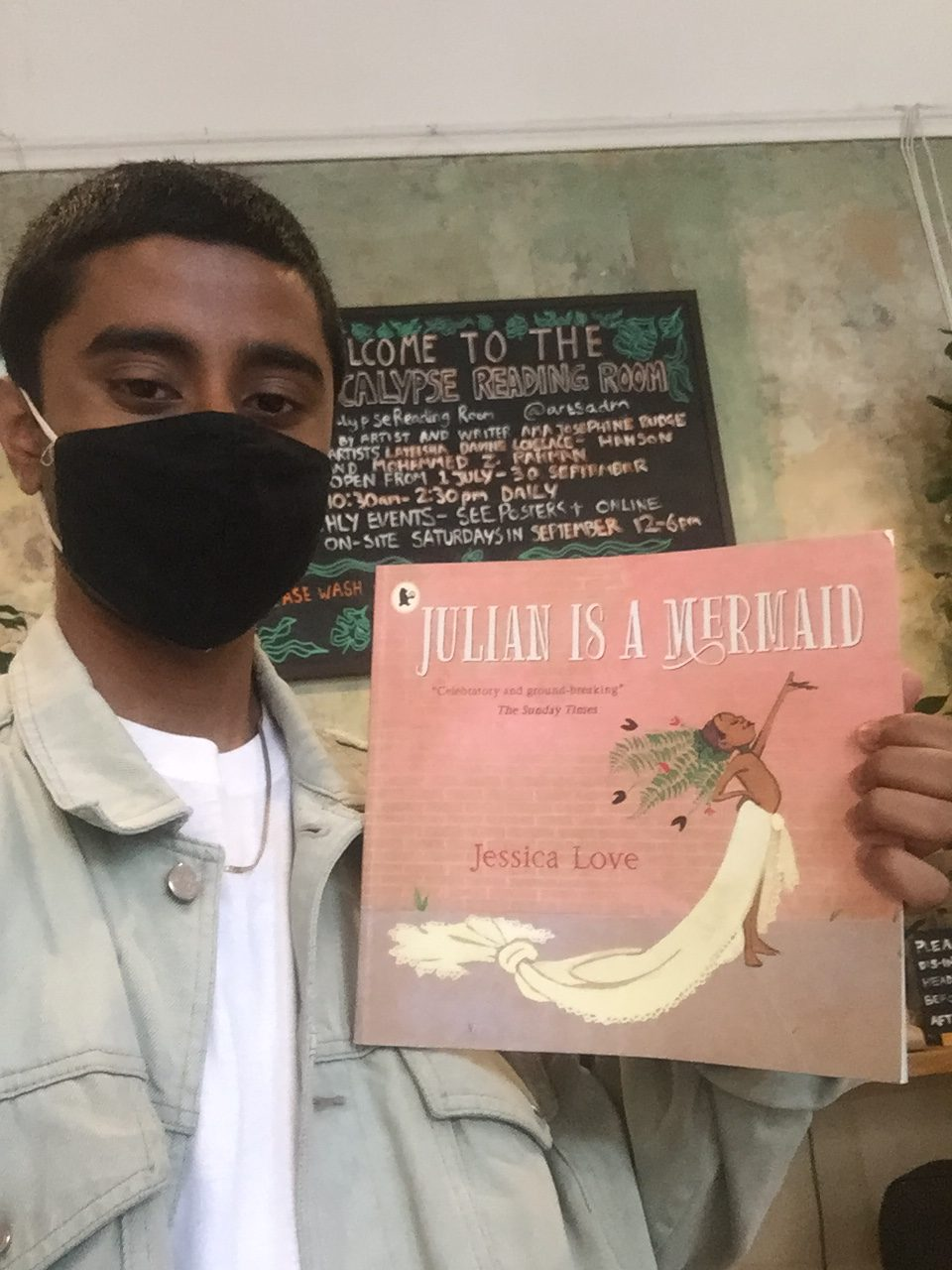 Mohammed holds up the book Julian is a Mermaid